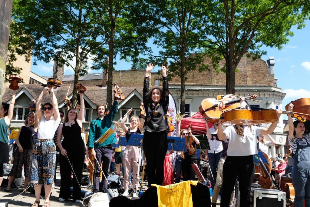Young musicians from Street Orchestra Live raise their instruments in the air after performing live in Oxford's Bonn Square on a sunny day in June 2019.